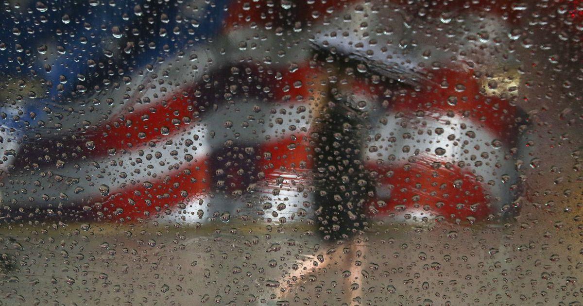 Жінка ходить із парасолькою під час дощу на тлі прапора США, намальованого на будівлі в Манхеттені у Нью-Йорку. @ Reuters