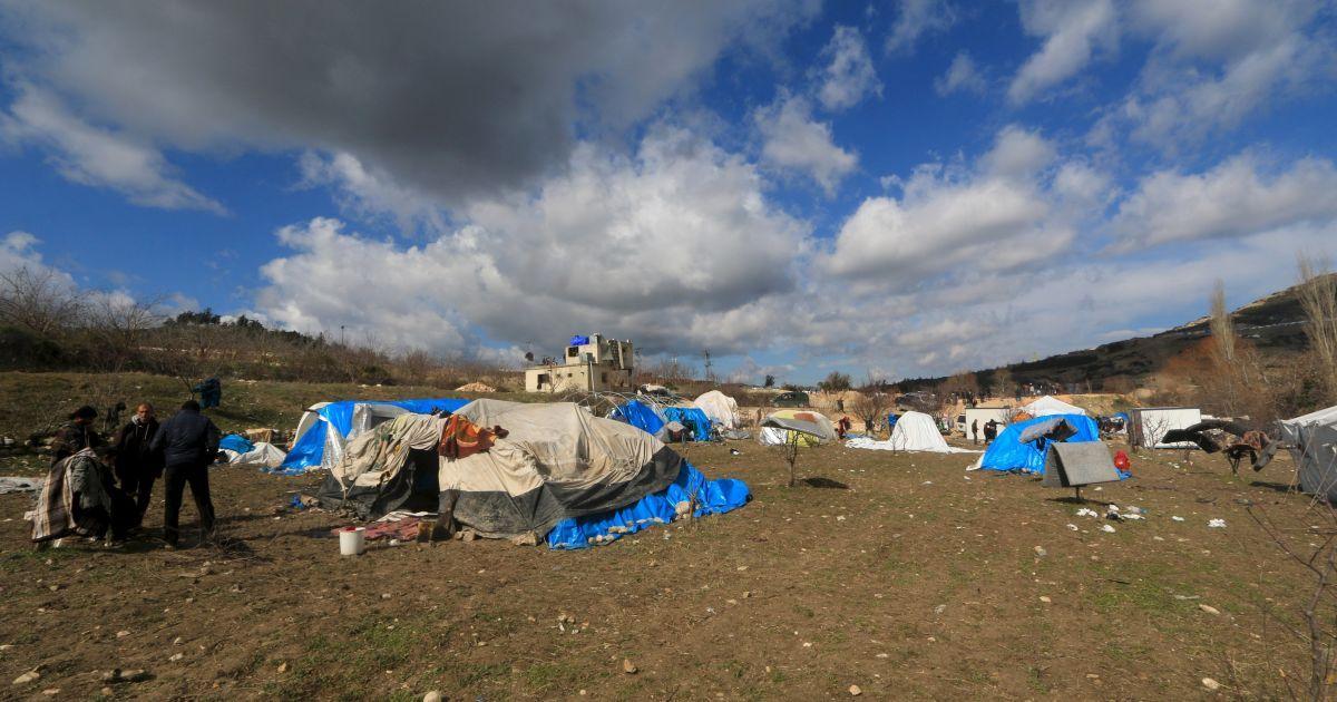 Люди стоять біля наметів для вимушених переселенців у місті Хірбет Аль-Джоз.