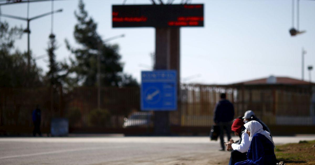 Люди сидять на тротуарі, на перетині кордону з Туреччиною, у південно-східному місті Кіліс.
