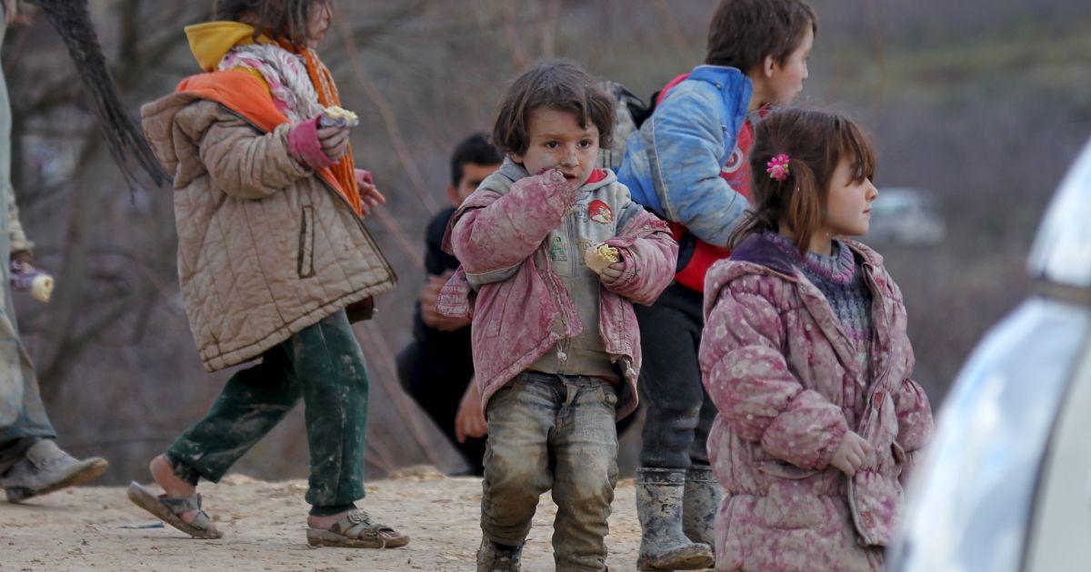Діти-біженці, усі в багнюці, чекають дозволу перетнути кордон в Туреччину зі своїми родинами у місті Хірбет Аль-Джоз.