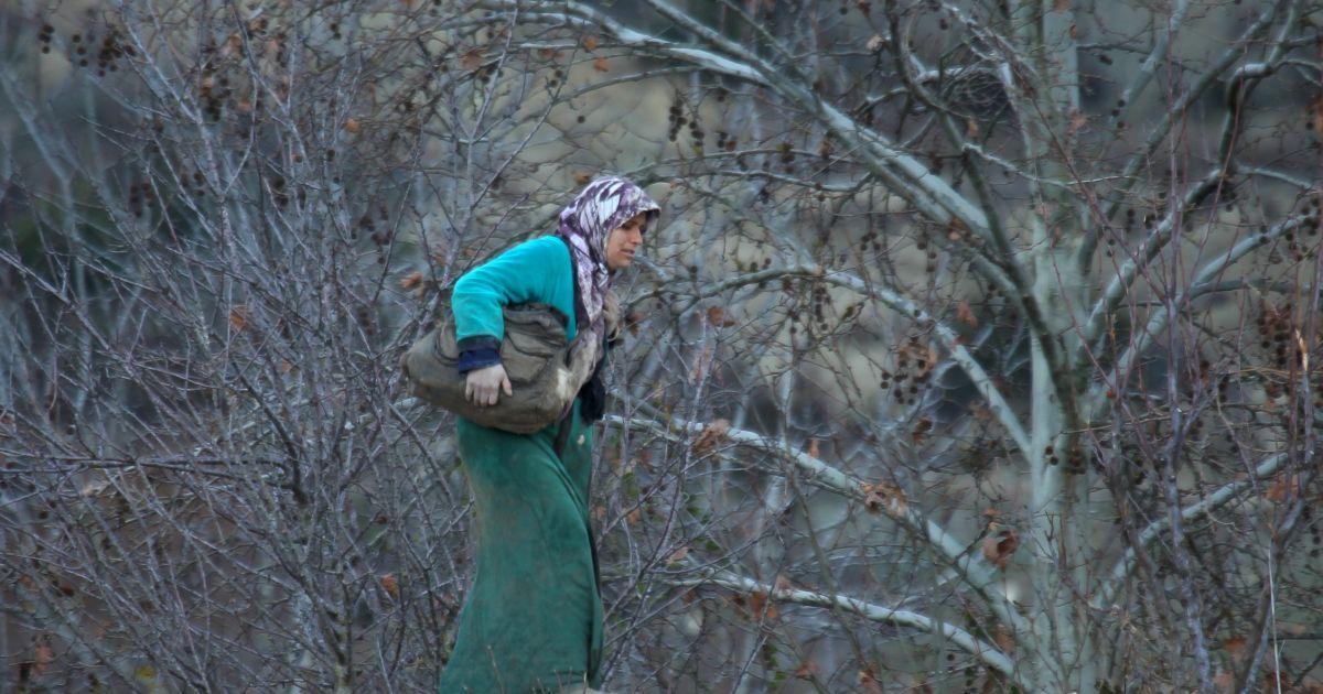 Сирійська жінка несе свої речі у місті Хірбет Аль-Джоз, чекаючи на дозвіл перетнути кордон з Туреччиною.