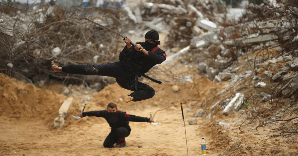 Палестинські молодики стрибають з мечами, демонструючи свої навички ніндзя серед руїн будівель, які були зруйновані в 2014 році під час війни в північній частині сектора Гази. @ Reuters