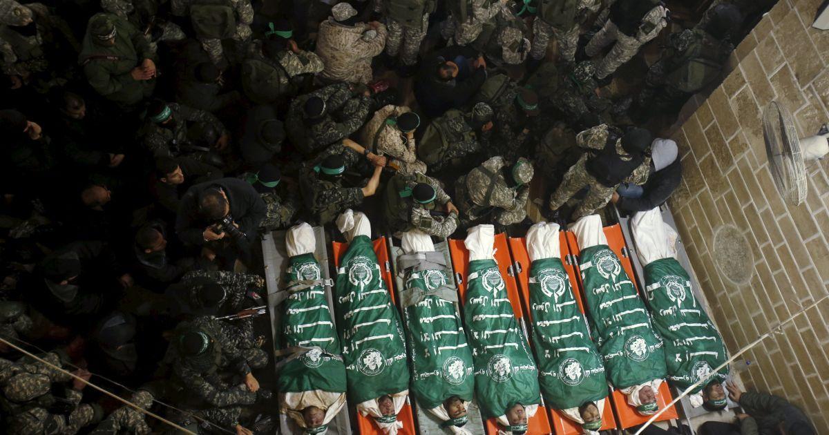 Палестинські бойовики ХАМАСу сидять поруч з тілами своїх товаришів, які загинули під час обвалення тунелю на східному кордоні сектора Газа з Ізраїлем. Семеро бойовиків загинули, намагаючись за допомогою тунелю атакувати ізраїльських військових. @ Reuters