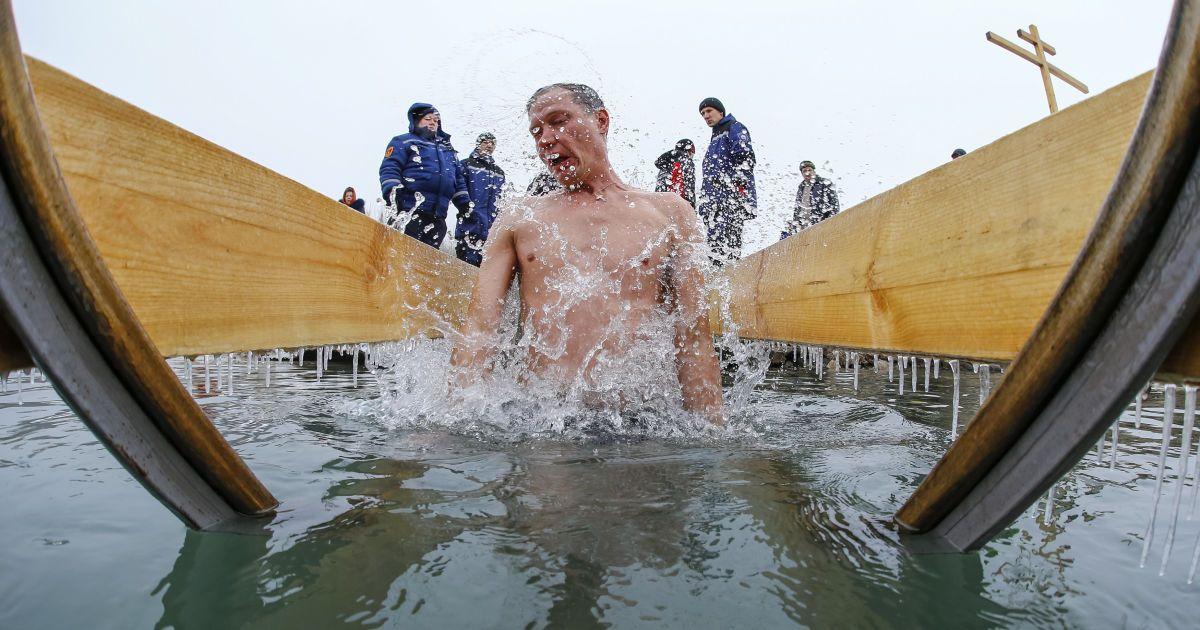 Чоловік занурюється у воду під час святкування Хрещення Господня на березі річки Велика Алматинка в Алмати, Казахстан. @ Reuters