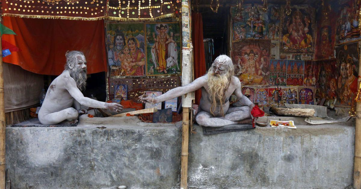 """Нага Садху або індуїстські святі мужі, змащені попелом, сидять у своїх тимчасових наметах недалеко від місця злиття річки Ганг і Бенгальської затоки під час фестивалю """"Макар Санкранті"""" на острові Сагар в Індії. @ Reuters"""