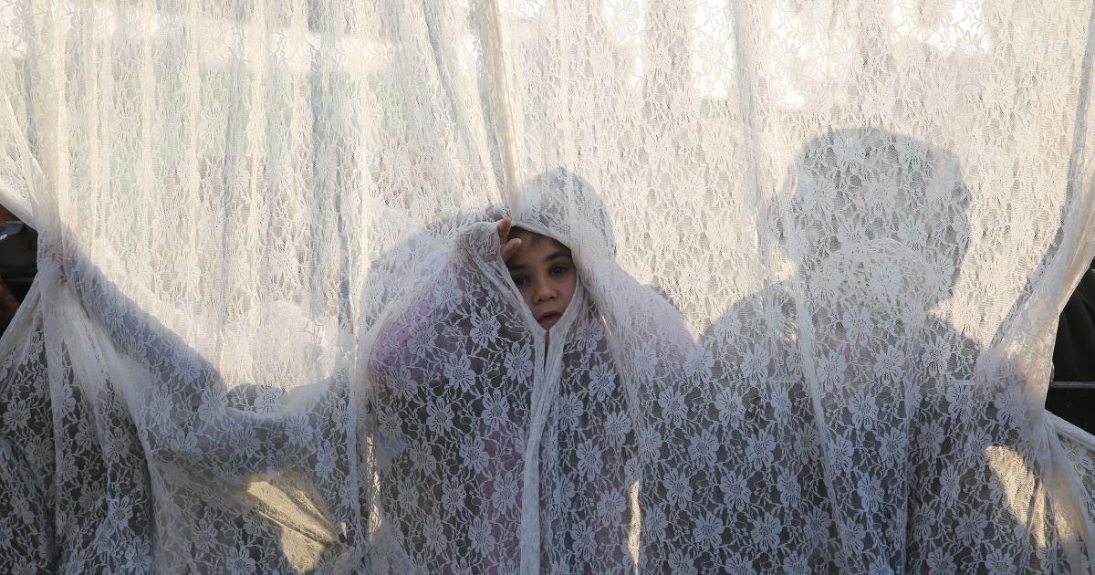 Дівчина стоїть за фіранкою, що відокремлює чоловіків і жінок на могилі рабина Ісраеля Абухазейра під час щорічного паломництва в річницю його смерті в південному ізраїльському місті Нетівот. @ Reuters