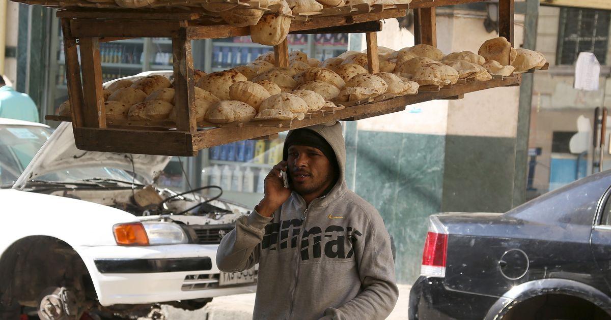 Працівник пекарні розмовляє по мобільному, несучи на голові піднос свіжоспеченого хліба з місцевої пекарні на вулиці в Каїрі, Єгипет. @ Reuters