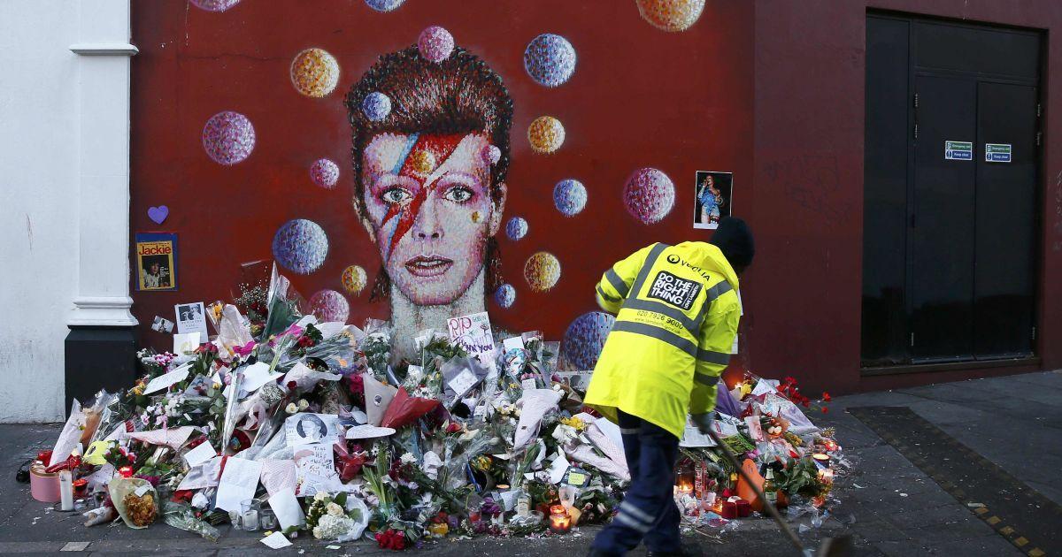 Працівник підмітає тротуар поруч з фрескою Девіда Боуї в Брікстоні, південному Лондоні, Великобританія. 69-річний співак помер від раку через два дні після випуску свого останнього альбому. @ Reuters