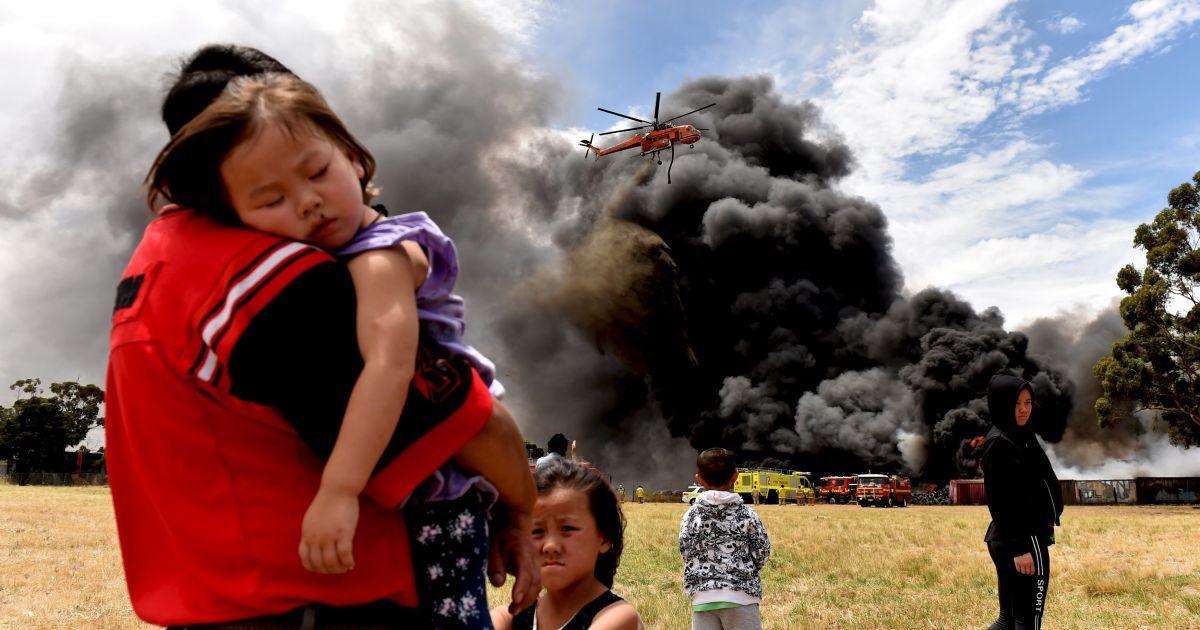 Місцеві жителі дивляться, як вертоліт гасить купу палаючих шин в Мельбурні, Австралія. @ Reuters