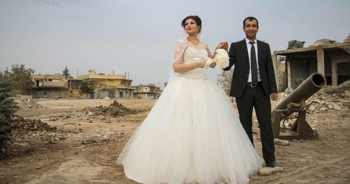 """Наречений тримає руку нареченої під час фотосесії поруч із зруйнованими будівлями у сирійському місті Кобані, перш ніж відправитися на їхню весільну церемонію. Ця курдська пара першою уклала цивільний шлюб у Кобані після того, як місто відвоювали у бойовиків """"Ісламської держави"""" і оголосили його частиною системи автономного самоврядування, встановленого курдами. @ Reuters"""