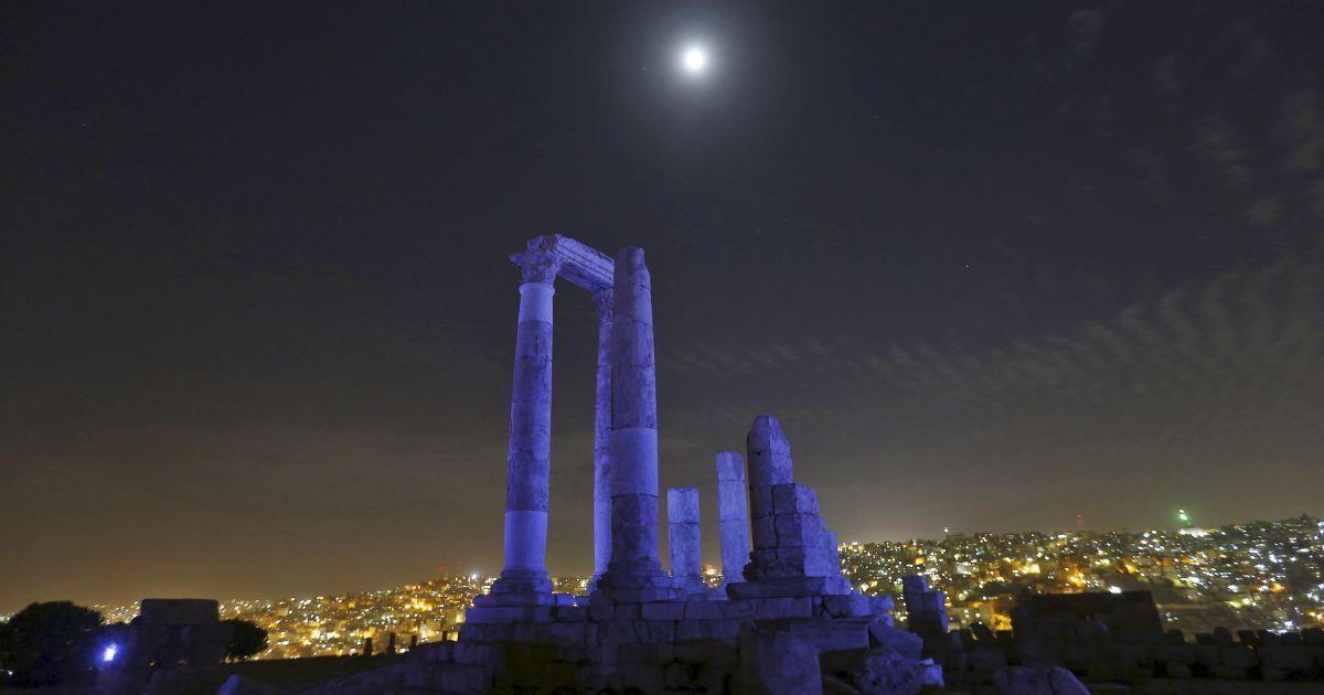Місяць видно через римські колони храму Геркулеса, які світяться синім на честь 70-річчя Організації Об'єднаних Націй в Цитаделі Аммана, Йорданія. @ Reuters