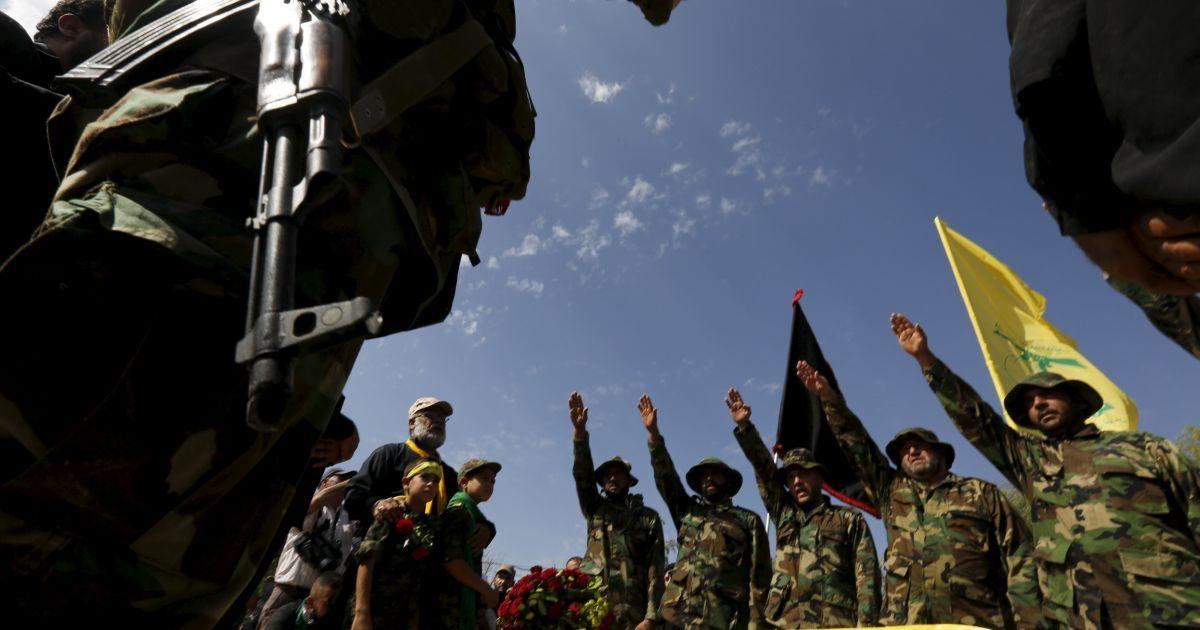 """Члени ліванського руху """"Хезболла"""" стоять з піднятими руками над труною їхнього сподвижника Аббаса Хамуда під час його похорону в селі Кфар-Кіла. Хамуд загинув під бою з бойовиками сирійської опозиції у провінції Ідліб. @ Reuters"""