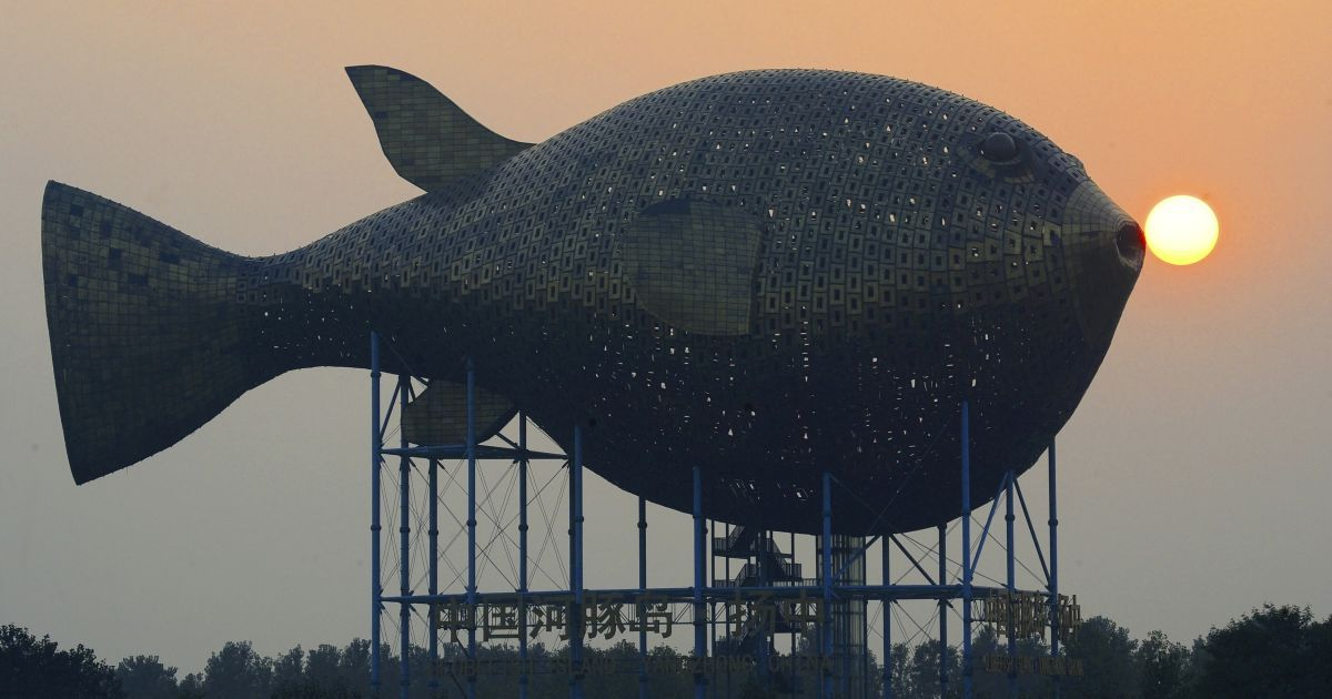 Сонце сідає за оглядовою вежею у формі гігантської риби на березі річки в окрузі Янгчонг провінції Цзянсу, Китай. Вежа складається з 8920 мідних пластин, вона має висоту 15 метрів. Її виготовлення коштувало близько 70 млн юанів ($ 11,4 млн). @ Reuters