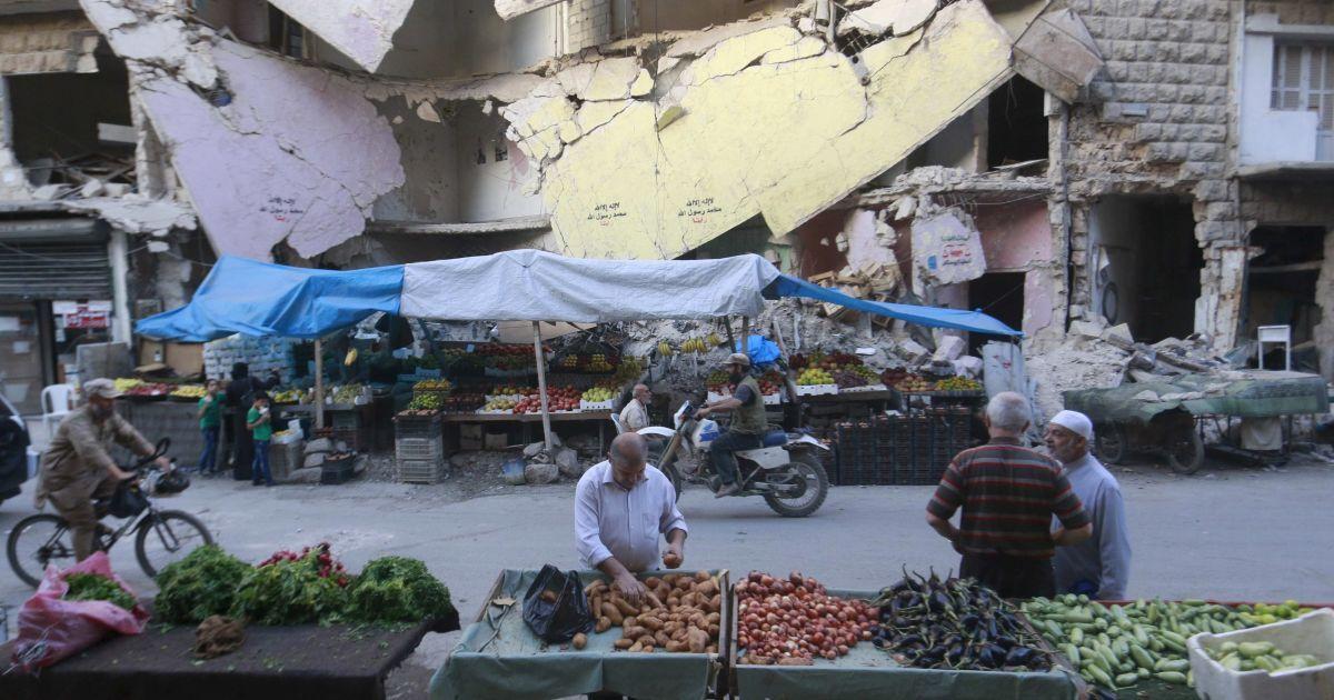 Магазин для овощей и фруктов на фоне перед поврежденных зданий в Бустан аль-Касре, окрестности Алеппо, Сирия. В стране уже более четырех лет продолжается гражданская война, которая унесла жизни более 220 000 человек. @ Reuters