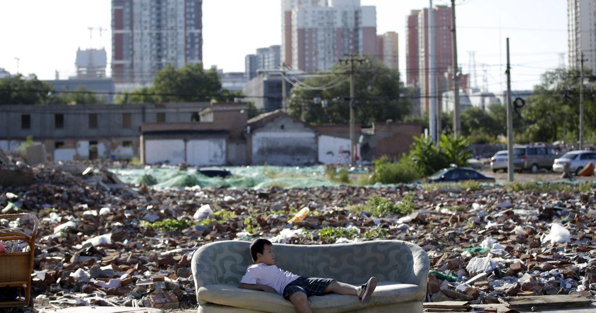 Мальчик играет на заброшенном диване в руинах снесенных домов в центре Пекина, Китай. @ Reuters