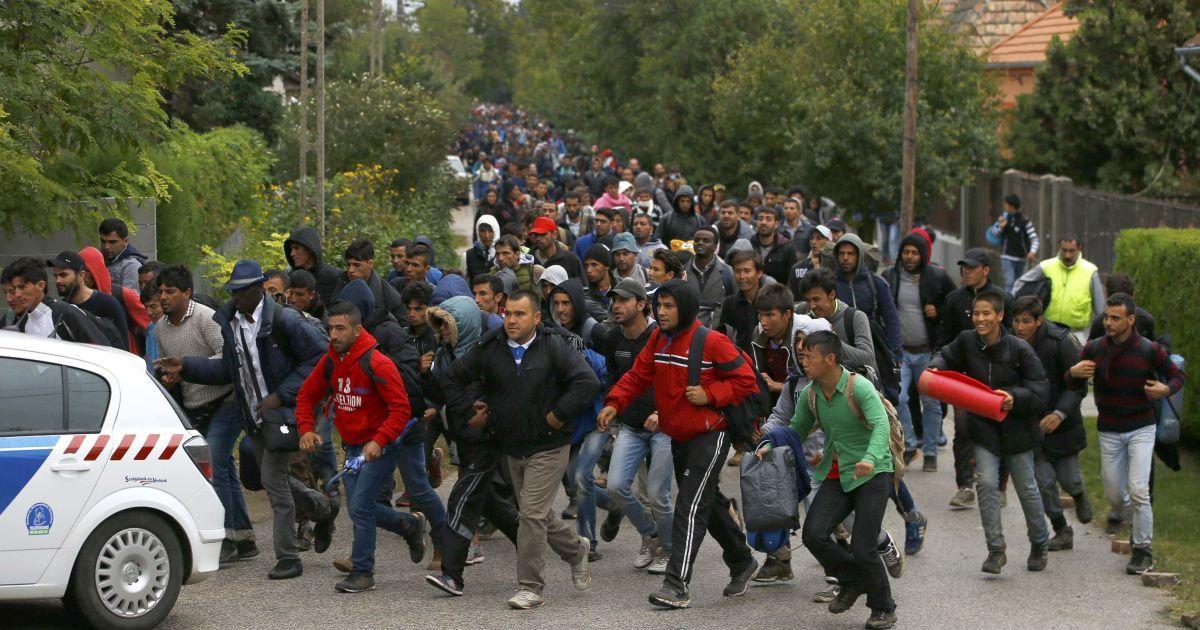Мигранты бегут за полицейским автомобилем в направлении к австрийской границе в селе Никкельсдорф, Венгрия. Ежедневно в Европу бегут в 8000 мигрантов и это может быть лишь верхушкой айсберга. Правительства должны работать, чтобы положить конец сирийской гражданской войне, чтобы предотвратить еще большую миграцию людей, заявило агентство ООН по делам беженцев в пятницу. @ Reuters