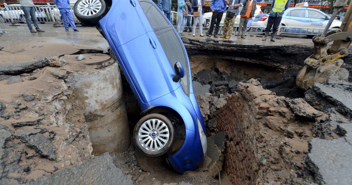 Автомобиль «попал» в водосточный колодец на улице в Ланьчжоу, что в китайской провинции Ганьсу. Водитель сумел выбраться невредимым @ Reuters