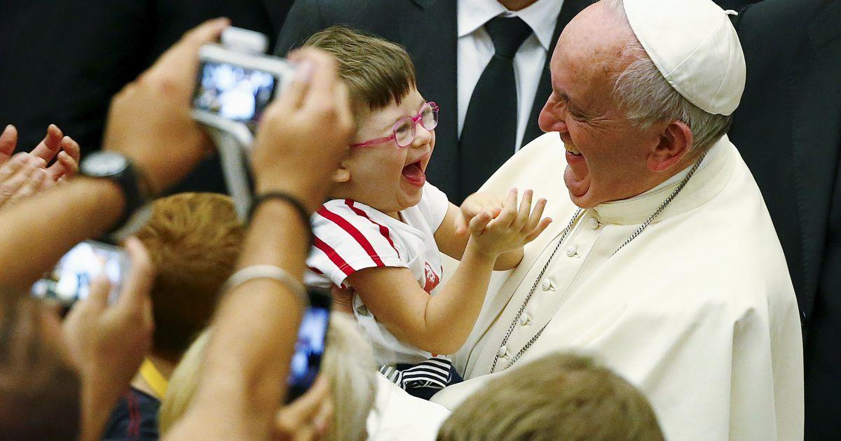 Папа Римский Франциск улыбается ребенку, которого взял на руки, во время аудиенции в Ватикане @ Reuters