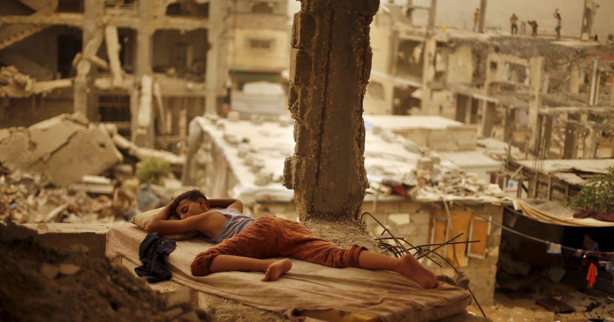 Палестинский мальчик спит на матрасе внутри останков дома его семьи, который, по словам свидетелей, был разрушен после израильского обстрела во время 50-дневной войны летом 2014-го @ Reuters