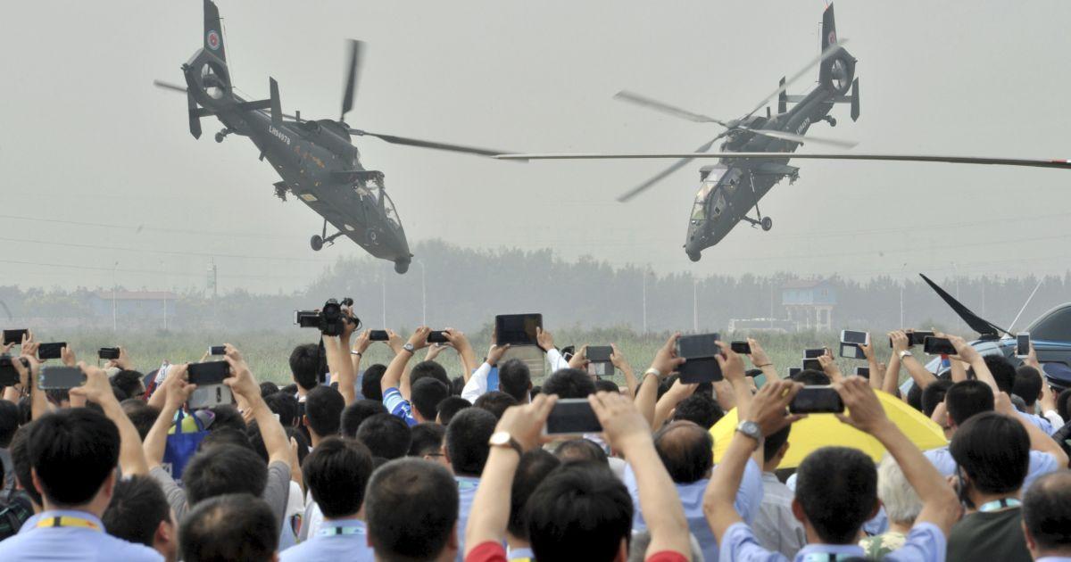 Зрители фотографируют на телефоны маневры вертолетов во время выставки военной техники в Китае @ Reuters