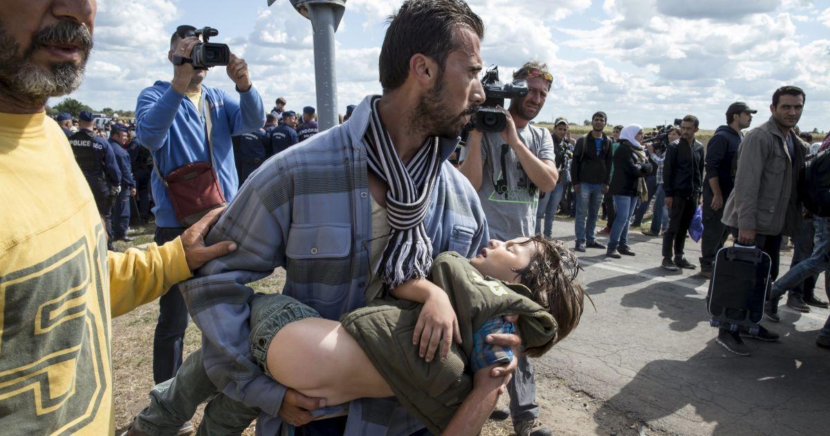 Мигрант несет на руках девочку, у которой произошел тепловой удар и которой нужна медицинская помощь. Фото сделано во временном лагере беженцев в селе Ресцке в Венгрии. В этой стране находятся около 50 тысяч мигрантов, которых ЕС пообещал перераспределить по всей Европе. Всего в ЕС сейчас находится до 160 тысяч беженцев @ Reuters