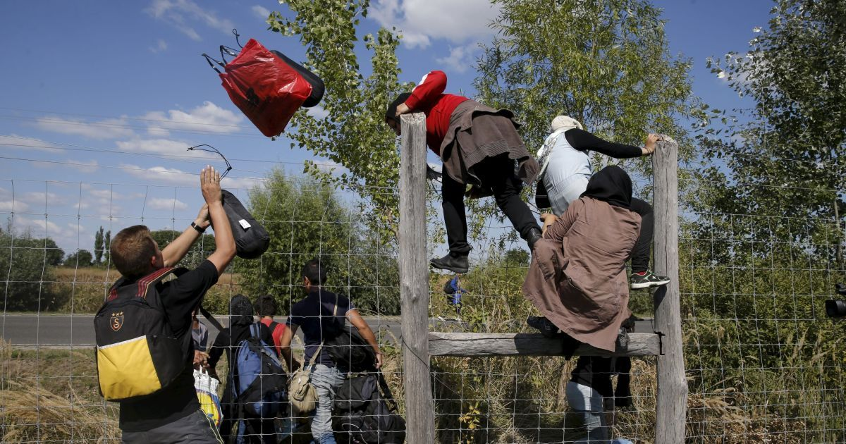 Мигранты перепрыгивают через забор, убегая из лагеря беженцев в Венгрии. С начала года в Европу приехали 365 тысяч беженцев, большинство которых – из Сирии, где продолжается война @ Reuters