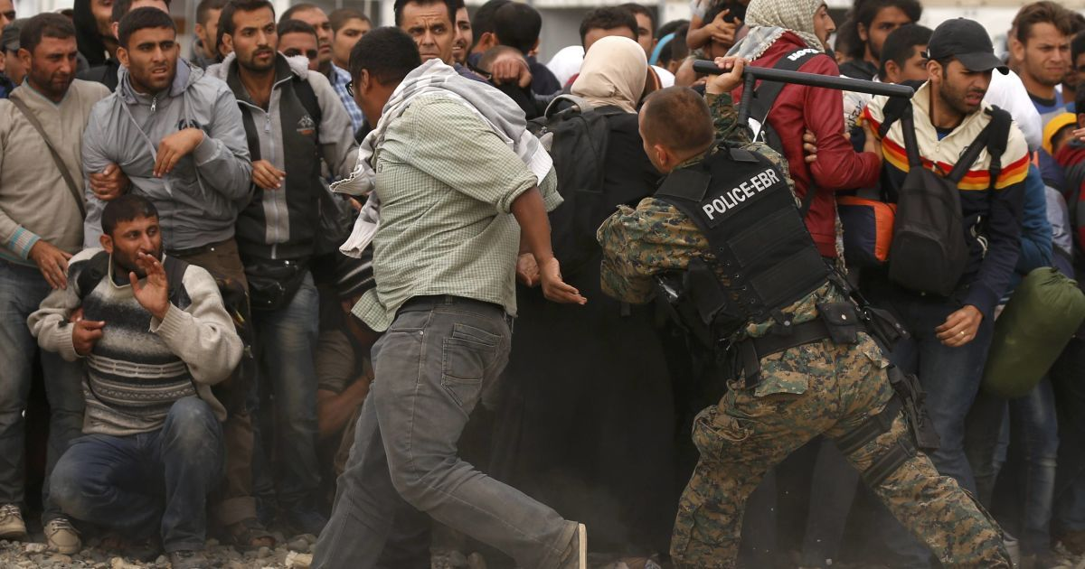 Полицейский замахивается дубинкой на мигранта, который пытался бежать к поезду. Фото сделано во временном лагере беженцев вблизи Гевгелии в Македонии. Сюда беженцы попадают из Сирии. Дальше их переправляют в Венгрию, а оттуда – перераспределяют по странам ЕС @ Reuters