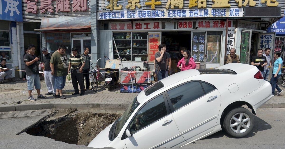 На улице в китайском Пекине автомобиль провалился в яму, которая внезапно возникла на дороге. Во время инцидента люди не пострадали @ Reuters