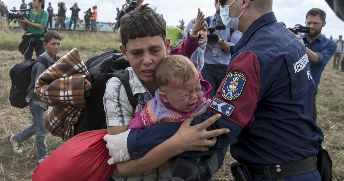 Венгерский полицейский пытается остановить мигранта с ребенком на руках, который хочет сбежать из лагеря беженцев в Венгрии @ Reuters