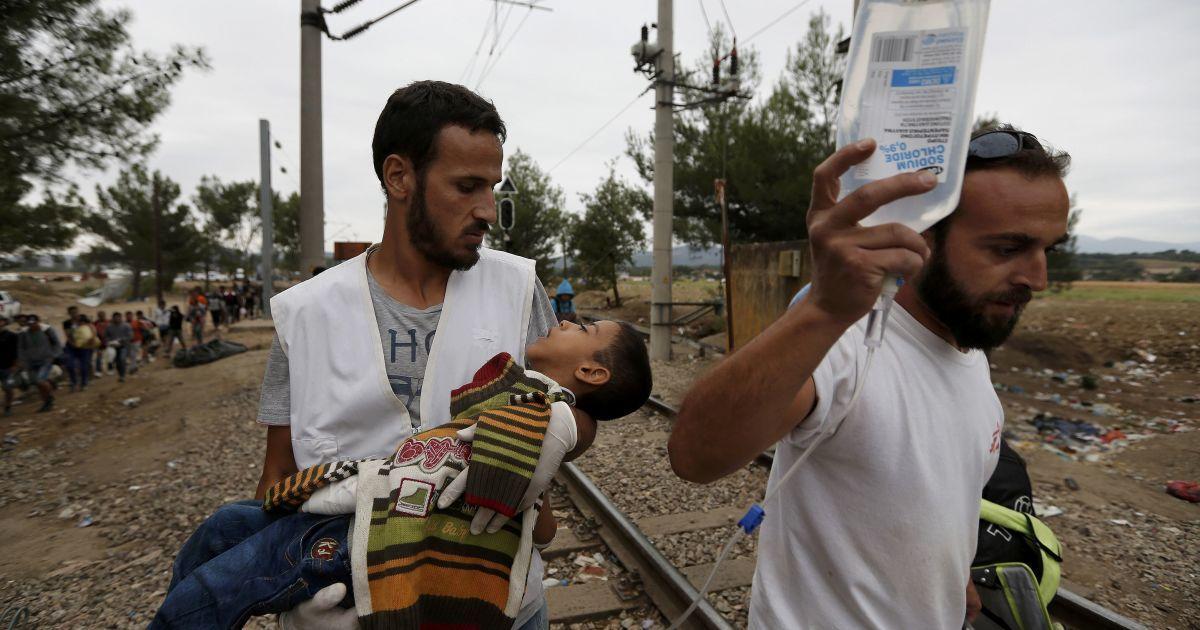 Медики несут тяжелобольного сирийского мальчика-беженца в лагере мигрантов на границе Греции и Македонии. С начала года в Европу приехали 365 тысяч беженцев, большинство которых – из Сирии, где продолжается война @ Reuters