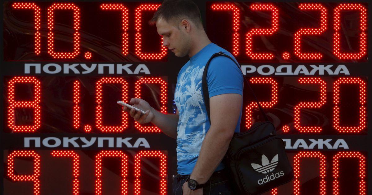 Мужчина смотрит в мобильный телефон, проходя мимо доски с курсами валют в Москве. В понедельник российский рубль достиг нового дна. Банк России установил курс доллара на 25 августа на уровне 70,75 рубля. курс евро на 25 августа составит 81,15 рубля. @ Reuters