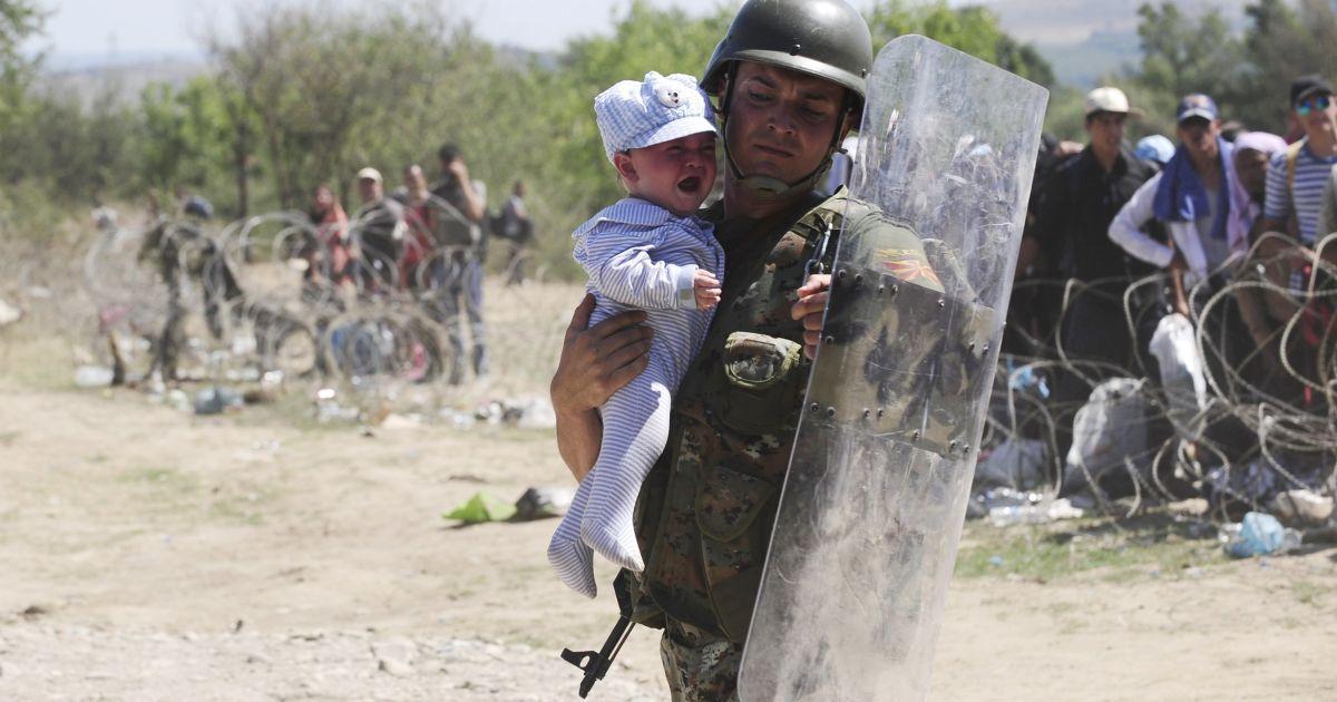 Полицейский несет ребенка в безопасное место. Мигранты пытаются попасть через границу в Македонию, а затем – в Западную Европу @ Reuters