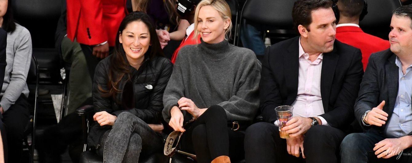 В свитере оверсайз и с сумкой Dior: Шарлиз Терон на баскетболе
