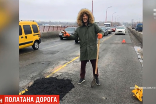 Пробитые колеса заставили водителей самостоятельно латать ямы на мосту в Днепре