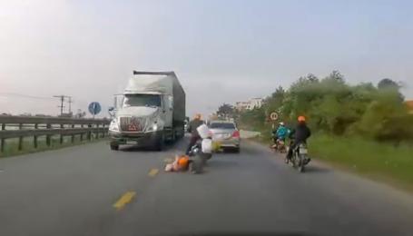 Мать и ребенок на скутере чудом спаслись от колес фуры во Вьетнаме