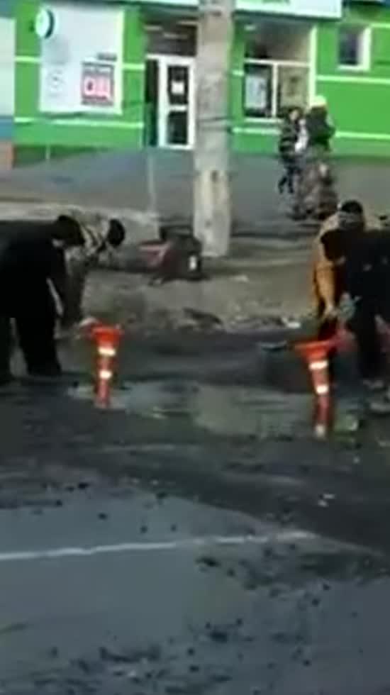 """Мережу обурило відео ремонту дороги у Чернівцях, з якої лопатами збирали воду у """"конуси"""""""