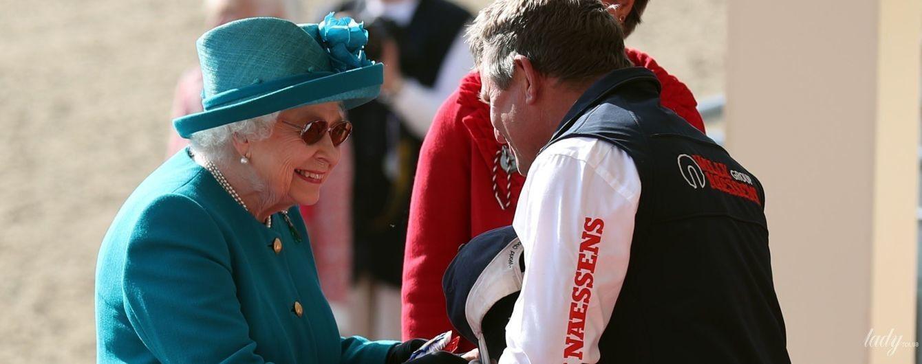 В бирюзовом пальто и шляпе: королева Елизавета II в красивом образе приехала на скачки
