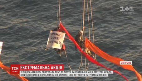 Активисты Greenpeace подвесили себя на мосту с требованием противодействовать изменению климата