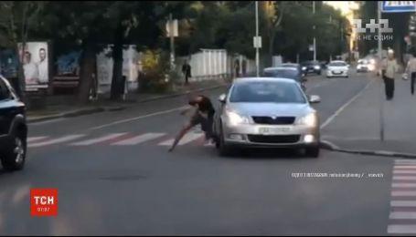 На столичному Подолі перехожі з правоохоронцями затримали чоловіка, який кидався на автомобілі