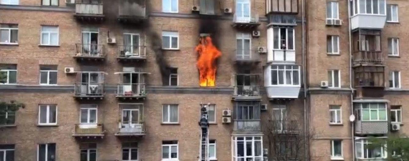 У центрі Києва масштабна пожежа охопила житлову квартиру, рятувальники евакуюють людей з будинку