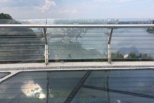 На пешеходном мосту Киева снова треснуло стекло