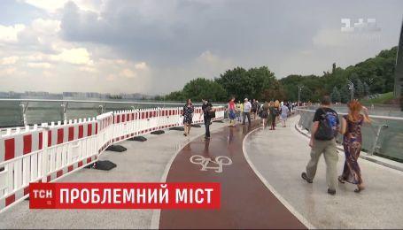 Новая травма: на пешеходном мосту в Киеве снова треснуло стекло