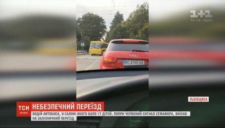 Несмотря на красный сигнал семафора, водитель автобуса с детьми выехал на железнодорожный переезд