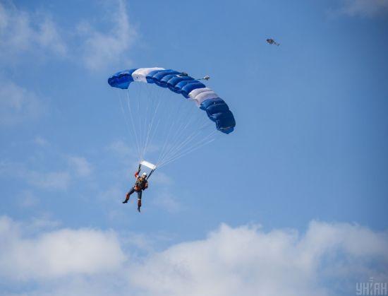 У РФ зафільмували військового, який стрибнув із парашутом і застряг на багатоповерхівці