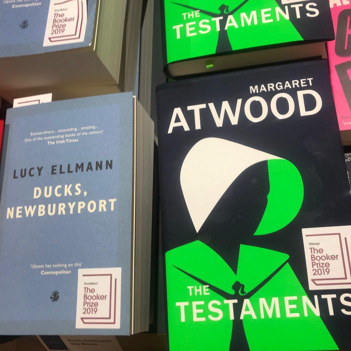 """На світлині дві книжки -""""Заповітом"""" Етвуд з наклейкою """"Переможець The Booker Prize 2019"""" такнижкаЛюсі Елманн""""Качки, Ньюберіпорт"""" із позначкою """"Фіналіст The Booker Prize 2019""""."""