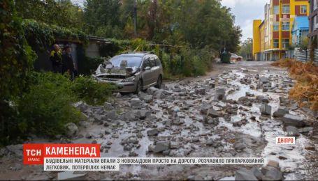Строительные материалы упали с новостройки в Днепре прямо на дорогу и повредили авто