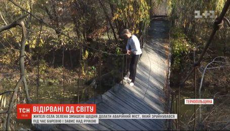 Селяне вынуждены ежедневно преодолевать аварийный мост, который разрушился во время урагана и завис над рекой