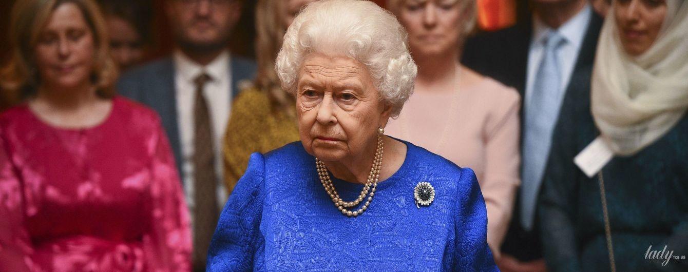 В неоново-синій сукні та з келихом: королева Єлизавета II на прийомі в палаці