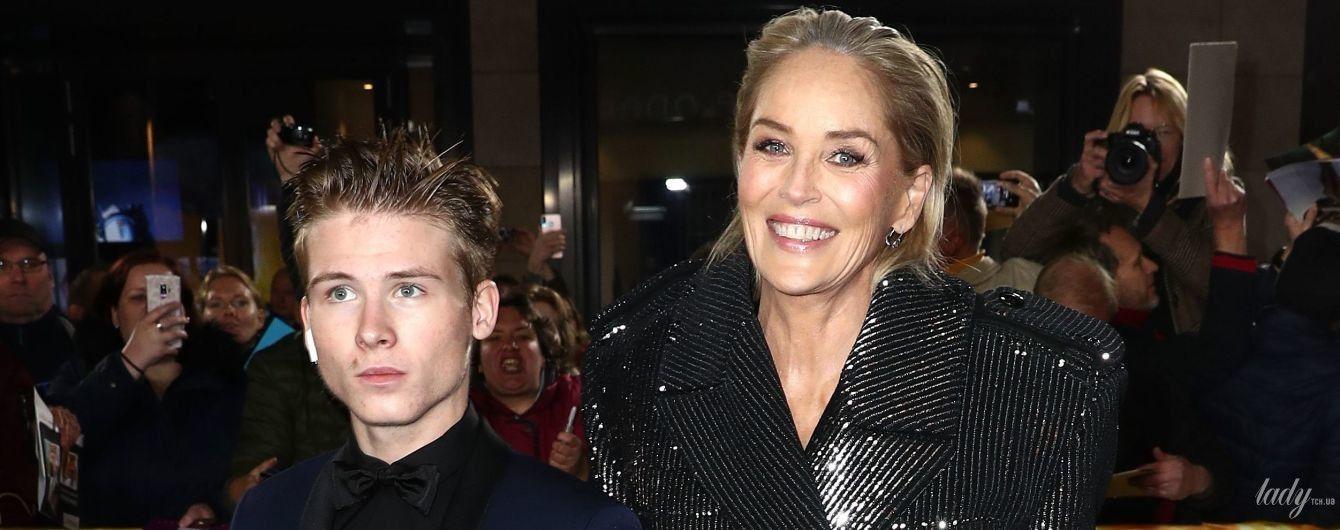 Вышла на дорожку с сыном: Шерон Стоун в блестящем пальто и платье с глубоким декольте приехала на церемонию