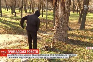 В Днепре злостных неплательщиков алиментов отправили на отработку. Родители убирают в парке